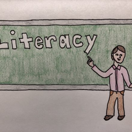 Teacher in front of blackboard that says Literacy